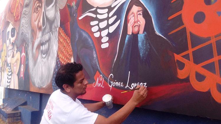 Noel Gómez trabajando en el mural que honra a Francisco Toledo